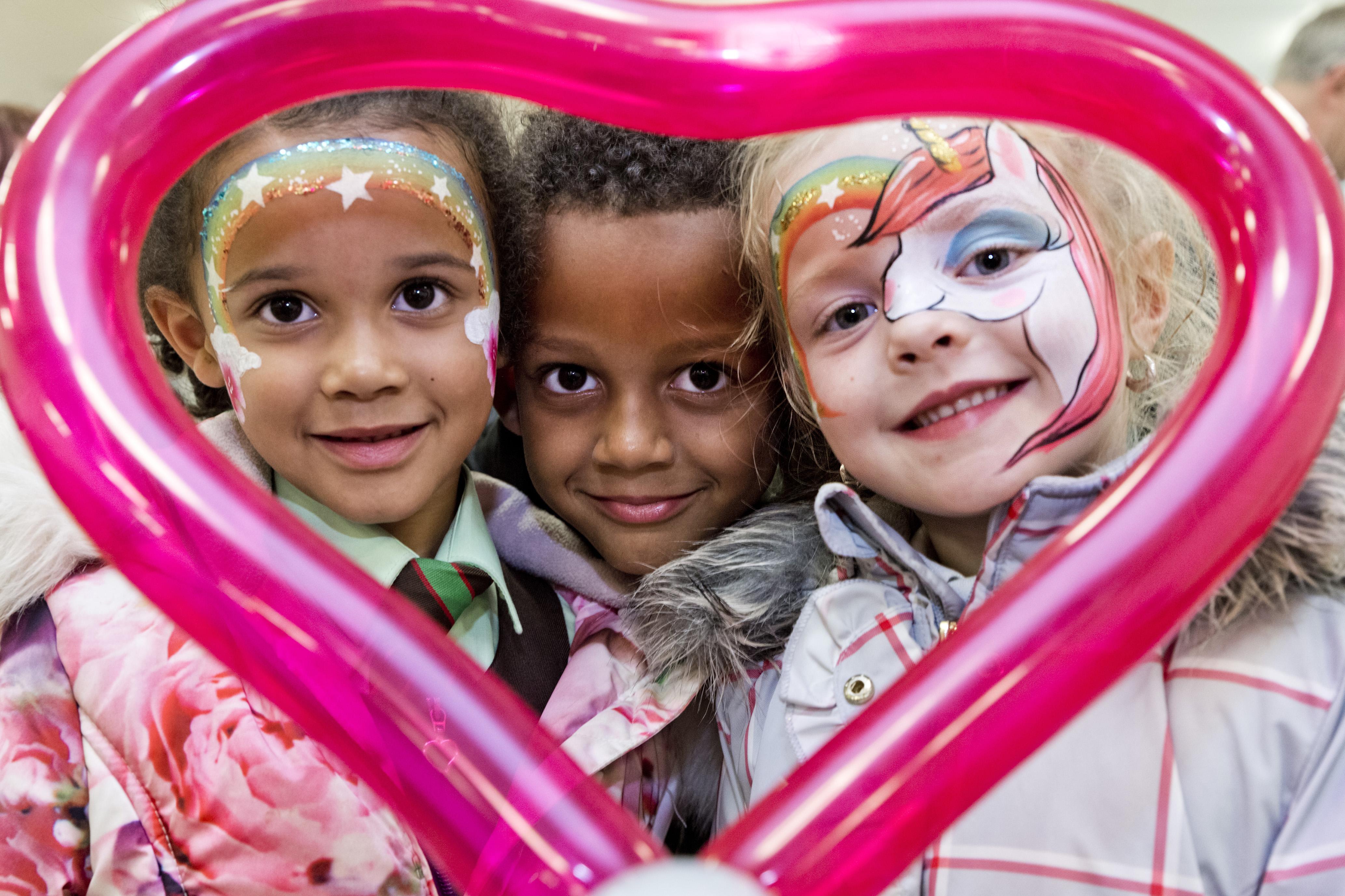 Young Kids Looking Through A Love Heart Ballon